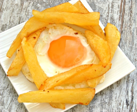 Fried egg with several chips served on a plate on wooden background Stock Photo - 12157619