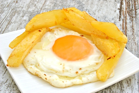 Fried egg with several chips served on a plate on wooden background Stock Photo - 12157618