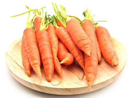 Carrots stacked side by side on wooden table, surrounded by white background photo