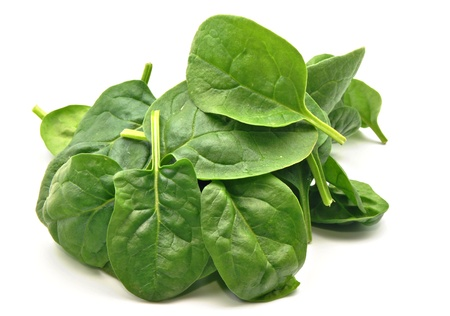 Spinach leaves stacked side by side surrounded by white background