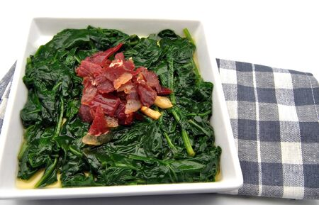 Spinach stew with ham and garlic on a dish towel photo