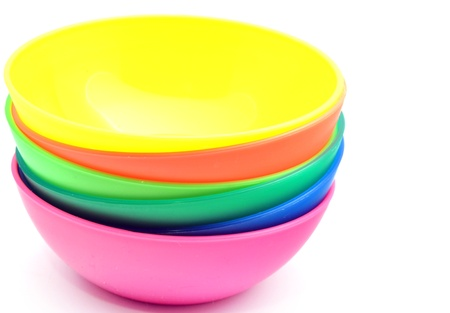 Bowls of various colors next to each other surrounded by white background photo