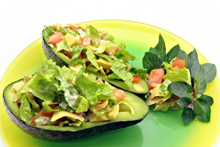 Stuffed avocados in a plate of colors, even side is a salad garnish photo
