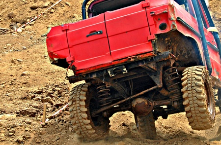 damping: Red road car jumping on dirt road
