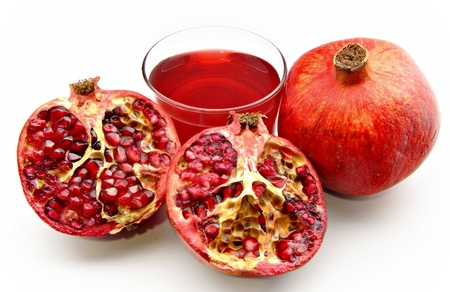 Halved pomegranate, one piece side by side with another grenade and a juice Stock Photo - 12536053