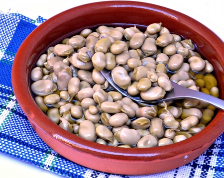 Beans with olive oil served in a pot on a blue cloth photo