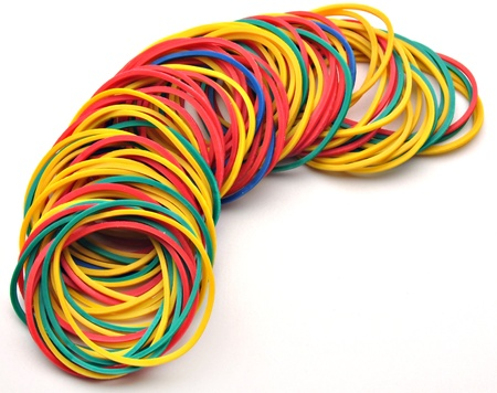 Colored rubber bands next to each other surrounded by white background Stock Photo
