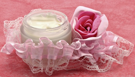 Pot of cream with a rose, surrounded by a ribbon on pink background photo