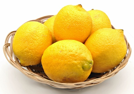 Several lemons in a basket surrounded by white background photo