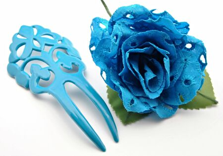 Comb and blue flowers surrounded by white background