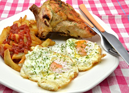 Roast chicken with potatoes and fried eggs photo