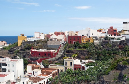urbanized: People of houses surrounded by banana trees and the sea beyond, is located in Garachico on the Spanish island of Tenerife