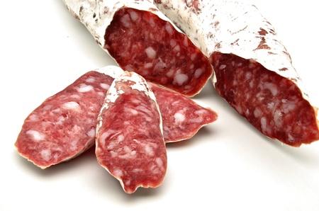 saucisse: Plusieurs pi�ces de Saucisson c�t� de l'autre entour� par un fond blanc Banque d'images