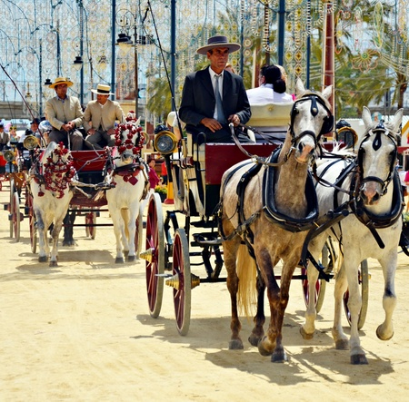 jerez: People in carriage horses walking in the royal house of the fair on the horse fair the day May 12, 2012 in Jerez de la Frontera, Spain  Editorial