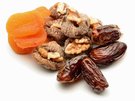 Figs, apricots, dates and walnuts surrounded by white background photo