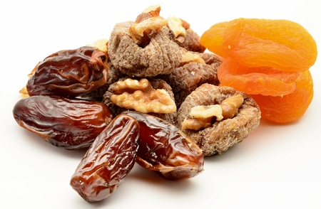 Figs, apricots, dates and walnuts surrounded by white background