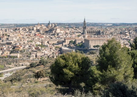 Cathedral of Santa Maria of the Spanish city of Toledo surrounded by the houses of the village, is a medieval city in the foreground are some trees photo