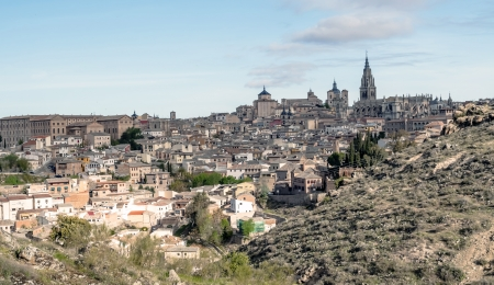 Cathedral and monastery of Santa Maria of the Spanish city of Toledo surrounded by the houses of the village, is a medieval city in the foreground are the mountains photo