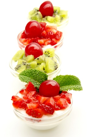 Yogurt with strawberries and kiwi located next to each other, surrounded by white background photo