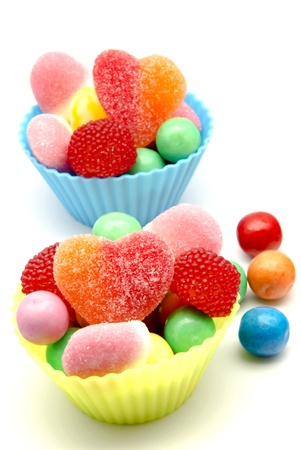 multicolored gumballs: Sugar candy into molds of muffins, surrounded by white background Stock Photo