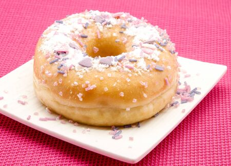 Donut decorated served on a plate surrounded by pink background Stock Photo - 14036532
