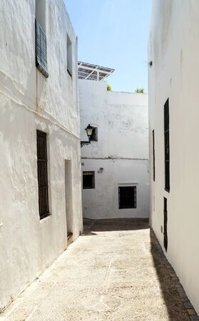 Close street decorated with white houses and bars in their windows It is Situated in a village in Spain Called Vejer de la Frontera photo