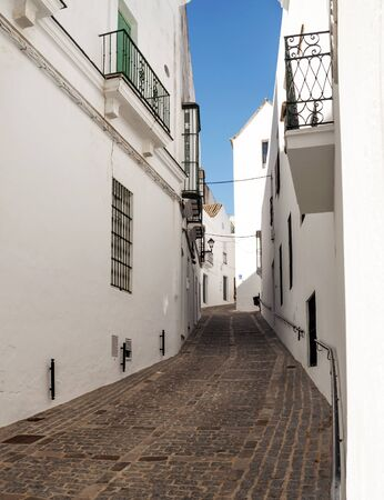 sloping: Close street decorated with white houses and bars in their windows  It is a narrow, sloping street  It is Situated in a village in Spain Called Vejer de la Frontera Stock Photo