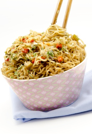 Eastern Pasta with vegetables with chopsticks on a napkin, surrounded by white background photo