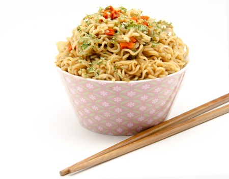 Eastern Pasta with vegetables with chopsticks, surrounded by white background photo
