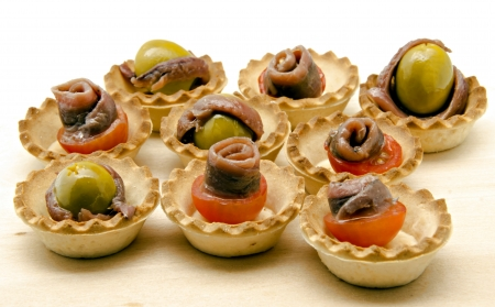 Snacks of olives, anchovies and tomatoes photo