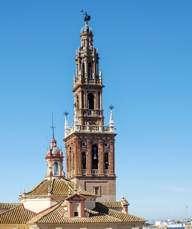 Bell tower of the church of San Bartolome located in the Spanish town of Carmona, are their bells together at the high of the church, is a picture vertically photo