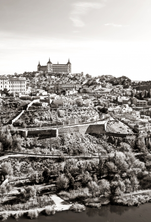 Distant view of the Alcazar in the Spanish city of Toledo, i is surrounded by monasteries and other houses forming a medieval town environment  It�s a vertical imagen with the tagus river   It�s a black and white imagen Stock Photo - 16649748
