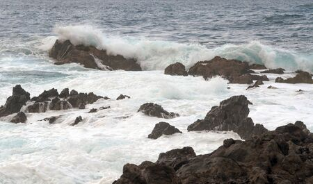 Waves in the sea surrounded by volcanic rocks photo