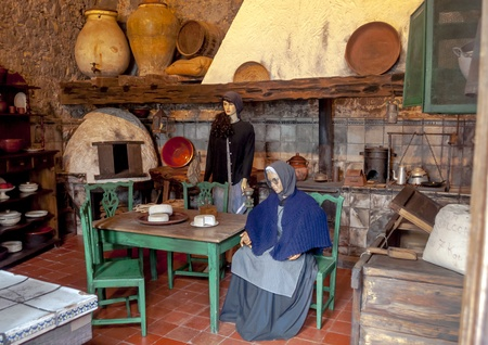 Old kitchen with two dolls