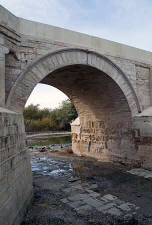 urbanized: View of the Tagus river under a bridge with stone buildings on the banks