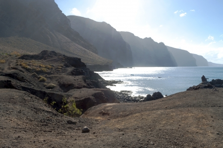 Beach next to a hillside with rocks in the sea in the village of Tenerife photo