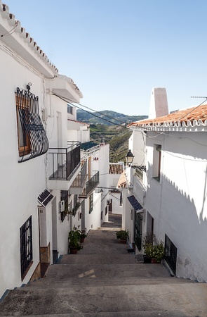 sloping: Street with white houses located in the town called Frigiliana, located in the Spanish province of Malaga, is a sloping street in vertical with the mountain in the background Editorial