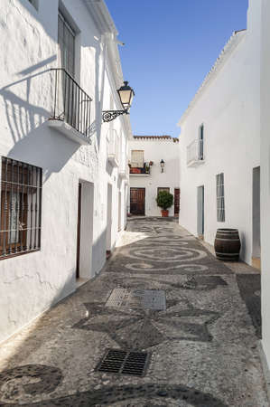 Street with white houses located in the town called Frigiliana, located in the Spanish province of Malaga, is a street with barrel in vertical