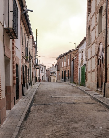 Street with houses located on the sides of Alaejos Spanish city in Spain, is a cloudy day. It is a picture vertically. photo
