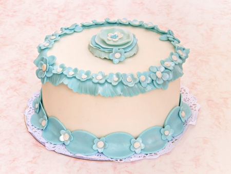 Wedding cake decorated with blue fondant flowers photo