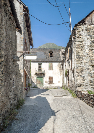 Street of Vielha village located in the Spanish province of Lleida . We see the facades of the houses with trees and balcony with flowers in the background. It�s a vertical picture. photo