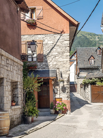 Street of Vielha village located in the Spanish province of Lleida . We see the facades of the houses with trees and mountains in the background in a sunny day. It�s a vertical picture. photo