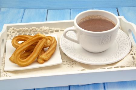 Cup of hot chocolate and several Churros photo