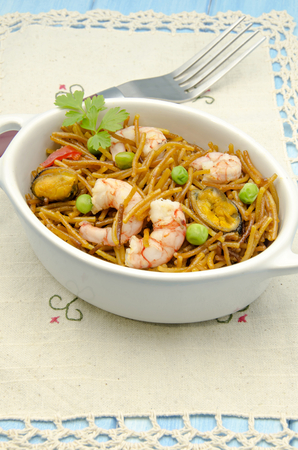 Noodles with seafood stew served in a casserole photo