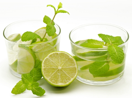Two mojito glasses decorated with mint and lime photo