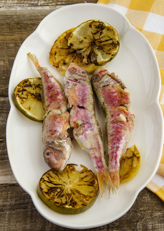 Several fresh mullet grilled with lemon slices photo