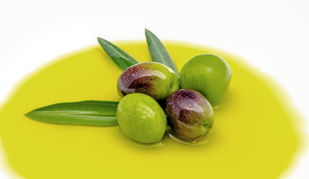 Extra virgin olive oil surrounded by freshly harvested olives photo