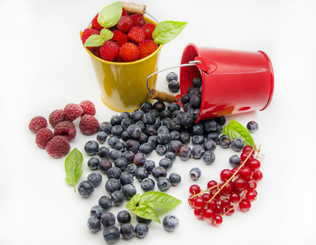 Varied assortment of fresh berries on white background photo