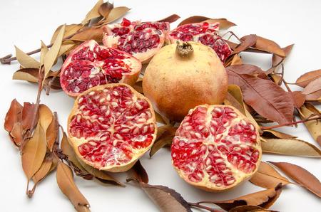 Fresh Pomegranates on background of autumn leaves
