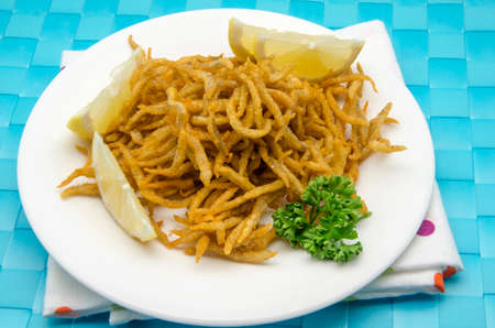 whitebait: Small fried whitebait served on a plate Stock Photo